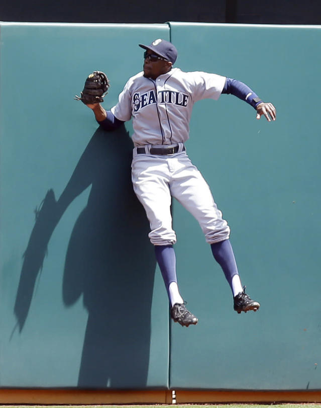 Seattle Mariners left fielder James Jones hits the wall after making the catch on a ball hit by Oakland Athletics' Josh Donaldson in the first inning of a baseball game Wednesday, May 7, 2014, in Oakland, Calif. (AP Photo/Ben Margot)