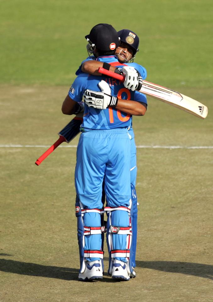 India's captain Virat Kohli (L) and teammate Suresh Raina embrace after victory during the 3rd match of the 5 cricket ODI series between Zimbabwe and India at Harare Sports Club on July 28, 2013. AFP PHOTO / JEKESAI NJIKIZANA        (Photo credit should read JEKESAI NJIKIZANA/AFP/Getty Images)