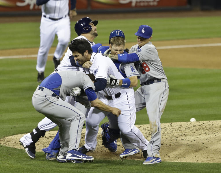 San Diego Padres' Carlos Quentin, center without hat, charges into Los Angeles Dodgers pitcher Zack Greinke, left foreground, after being hit by a pitch in the sixth inning of baseball game in San Diego, Thursday, April 11, 2013. (AP Photo/Lenny Ignelzi)