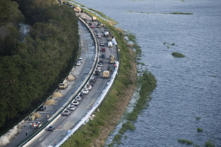 As traffic heads to the beach emergency crews build a temporary dam protecting U.S. 501 from floodwaters after Hurricane Florence struck the Carolinas Monday, Sept. 17, 2018, in Conway, S.C. (AP Photo/Sean Rayford)