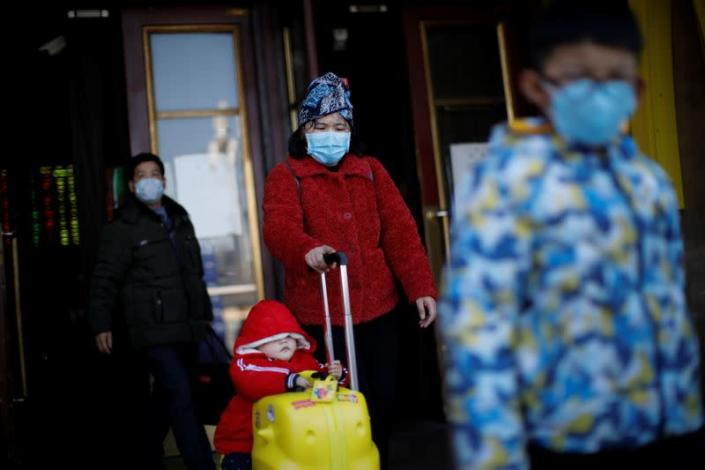 People wearing face masks carry their luggage as they walk outside Beijing Railway Station as the country is hit by an outbreak of the new coronavirus, in Beijing