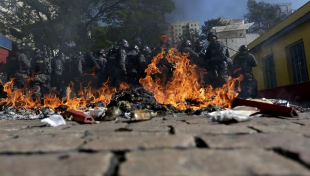 Riot policemen stand behind burning rubbish during a protest against the 2014 World Cup in Sao Paulo June 12, 2014. REUTERS/Ricardo Moraes (BRAZIL - Tags: SPORT SOCCER WORLD CUP CIVIL UNREST)