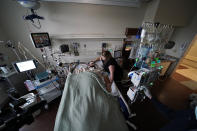 Lauren Debroeck, who is on oxygen as she recovers from COVID-19, talks to her husband, Michael, who also contracted COVID-19 and is being kept alive with the help of an oxygenation machine, at the Willis-Knighton Medical Center in Shreveport, La., Wednesday, Aug. 18, 2021. (AP Photo/Gerald Herbert)