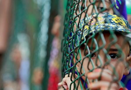 Kashmiri child looks from behind a fence at a protest site in Srinagar