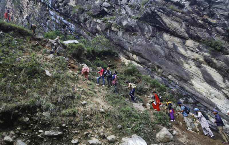 Stranded pilgrims climb in a row as they are evacuated by Indian army soldiers in Govindghat, India, Saturday, June 22, 2013. Soldiers were working to evacuate tens of thousands of people still stranded Saturday in northern India where nearly 600 people have been killed in monsoon flooding and landslides. (AP Photo/Rafiq Maqbool)