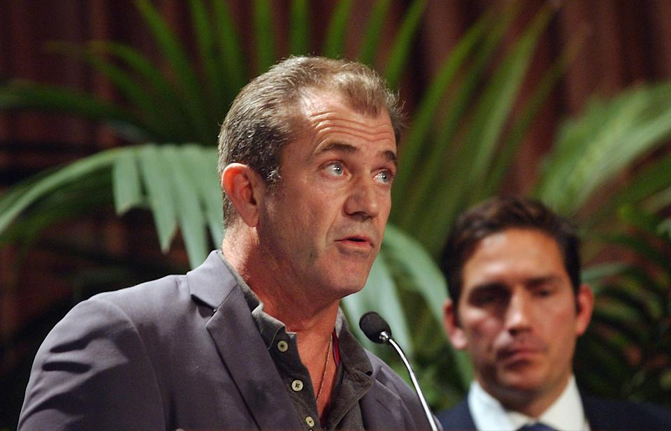 """Actor/Director Mel Gibson, left, talks about his film """"The Passion of the Christ"""" as Jim Caviezel, left, who portrayed Jesus, looks on after Gibson accepted the Motion Picture Award during the Catholics in Media Awards ceremony, Sunday, Nov. 7, 2004, in Beverly Hills, Calif.  Gibson and Caviezel were several people in the television and film industry who received awards from the Catholics in Media Associates, which recognizes people and projects that uplift and inspire. (AP Photo/Rene Macura)"""