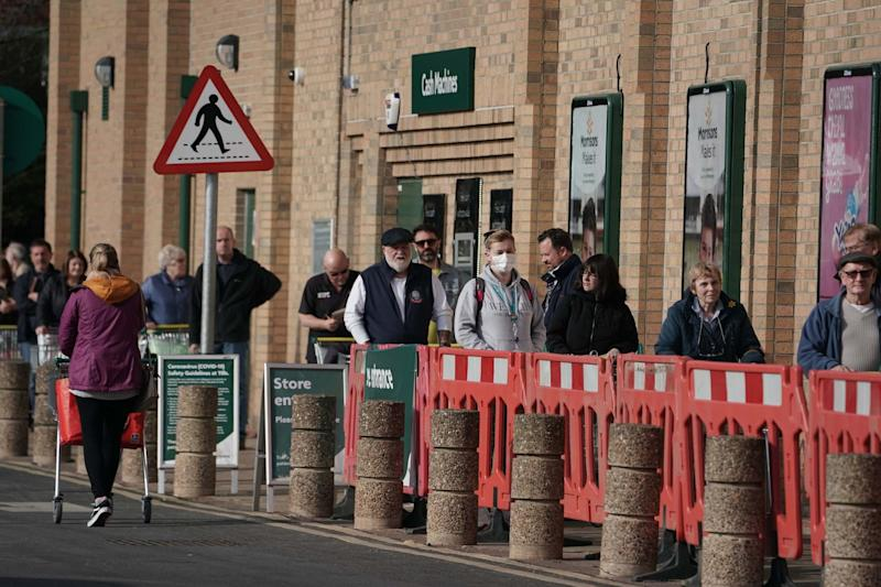 Customers queue outside a supermarket in Whitley Bay: PA