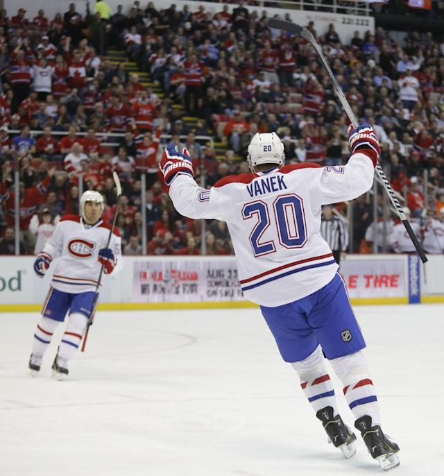 Montreal Canadiens' Thomas Vanek (20) of Austria, and teammate Francis Bouillon, left, celebrate a goal by David Desharnais during the second period of an NHL hockey game against the Detroit Red Wings Thursday, March 27, 2014, in Detroit. (AP Photo/Duane Burleson)
