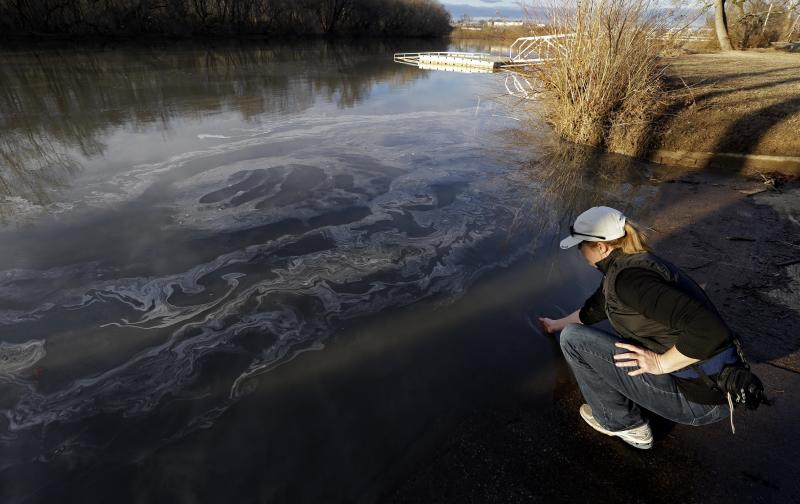In this Wednesday, Feb. 5, 2014 photo, Amy Adams, North Carolina campaign coordinator with Appalachian Voices dips her hand into the Dan River in Danville, Va. as signs of coal ash appear in the river. Duke Energy estimates that up to 82,000 tons of ash has been released from a break in a 48-inch storm water pipe at the Dan River Power Plant in Eden N.C. Over the last year, environmental groups have tried three times to use the federal Clean Water Act to force Duke Energy to clear out leaky coal ash dumps. Each time, the N.C. Department of Environment and Natural Resources has effectively halted the lawsuit by intervening at the last minute to assert its own authority to take enforcement action. In two cases, the state has proposed modest fines but no requirement that the nation's largest electricity provider actually clean up the coal ash ponds. The third case is pending. (AP Photo/Gerry Broome)