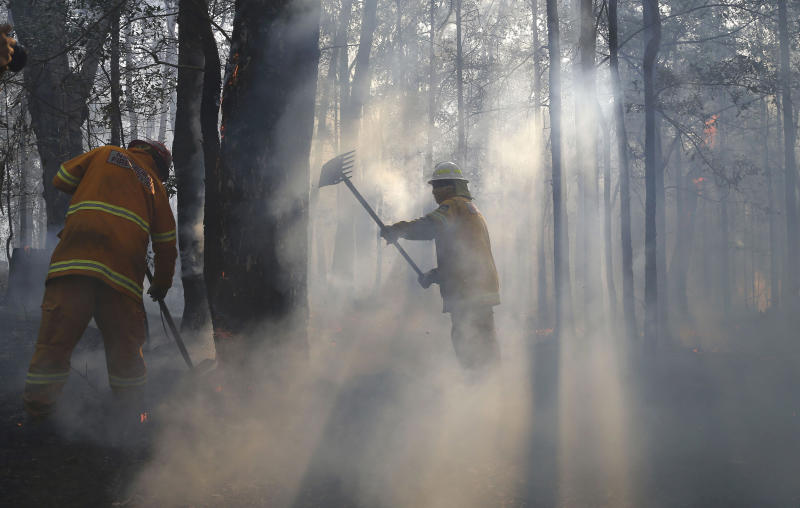 Firefighters mop up and check for reflash after a firestorm swept through a property in Bilpin, 75 kilometers (47 miles) from Sydney, Wednesday, Oct. 23, 2013. Scores of Australians evacuated their homes in mountains west of Sydney on Wednesday as intensifying winds fanned wildfires and grounded the helicopters that were fighting them. (AP Photo/Rob Griffith)