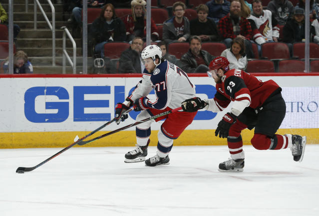 Columbus Blue Jackets right wing Josh Anderson (77) shields the puck from Arizona Coyotes defenseman Oliver Ekman-Larsson in the first period during an NHL hockey game, Thursday, Feb. 7, 2019, in Glendale, Ariz. (AP Photo/Rick Scuteri)