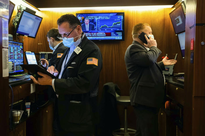 In this photo provided by the New York Stock Exchange, traders work in a booth on the trading floor, Wednesday, Jan. 20, 2021. U.S. stocks are rallying to records Wednesday on encouraging earnings reports and continued optimism that new leadership in Washington will mean more support for the struggling economy. (Colin Ziemer/New York Stock Exchange via AP)