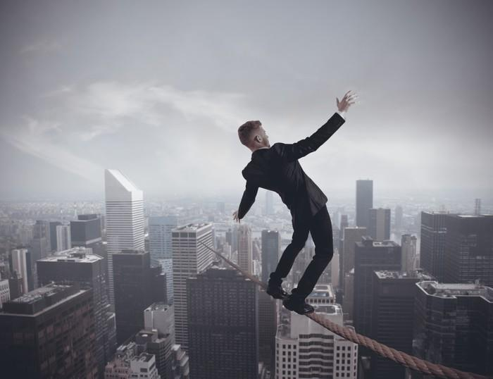 A businessman standing on a wire strung high above a bustling cityscape.
