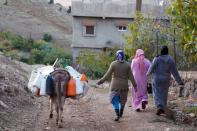 Three women walk with their donkey carrying plastic containers of water to their homes in the community of Ait Hammou Ouhmad on the edge of Azrou