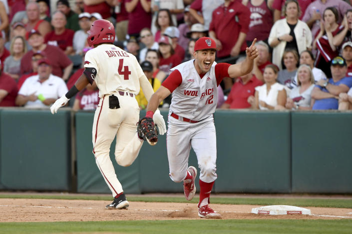 North Carolina State first baseman Austin Murr (12) reacts after making the game ending out on Arkansas base runner Jalen Battles (4) as they win 3-2 to and advance to the College World Series during an NCAA college baseball super regional game Sunday, June 13, 2021, in Fayetteville, Ark. (AP Photo/Michael Woods)