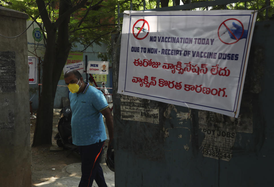 FILE - In this May 3, 2021, file photo, an Indian man walks through a gate that displays a banner with information about vaccine shortages outside a primary health center in Hyderabad, India. The Biden administration plans to provide 500 million shots purchased from Pfizer to 92 lower income countries and the African Union over the next year through the U.N.-backed COVAX program. (AP Photo/Mahesh Kumar A., File)