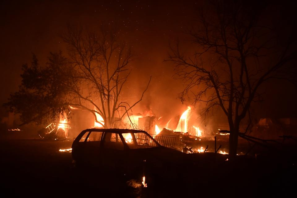 A fire burns a house in Adames area, in northern Athens, Greece, Tuesday, Aug. 3, 2021. Thousands of people fled their homes north of Athens on Tuesday as a wildfire broke out of the forest and reached residential areas. The hurried evacuations took place just as Greece grappled with its worst heat wave in decades. (AP Photo/Michael Varaklas)