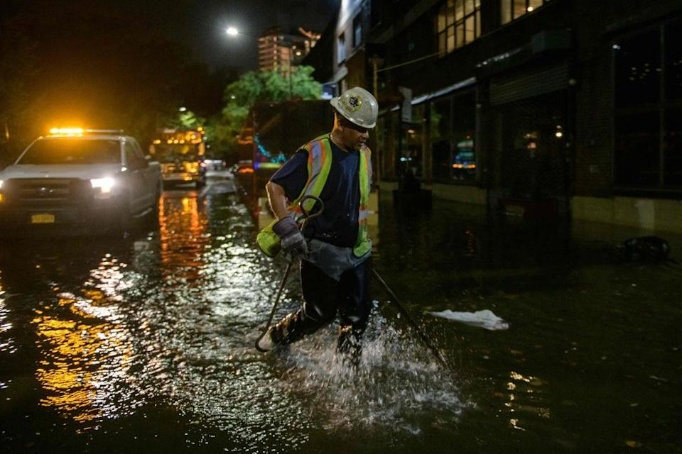 A worker unblocks drains on a street affected by floodwater in Brooklyn, New York early on September 2, 2021, as flash flooding and record-breaking rainfall brought by the remnants of Storm Ida swept through the area (AFP via Getty Images)