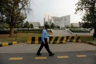 FILE PHOTO: A policeman walks past the Supreme Court building in Islamabad