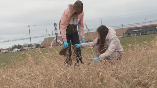 Ryan Newson, left, and Maia MacLean pick up garbage from a nearby field.