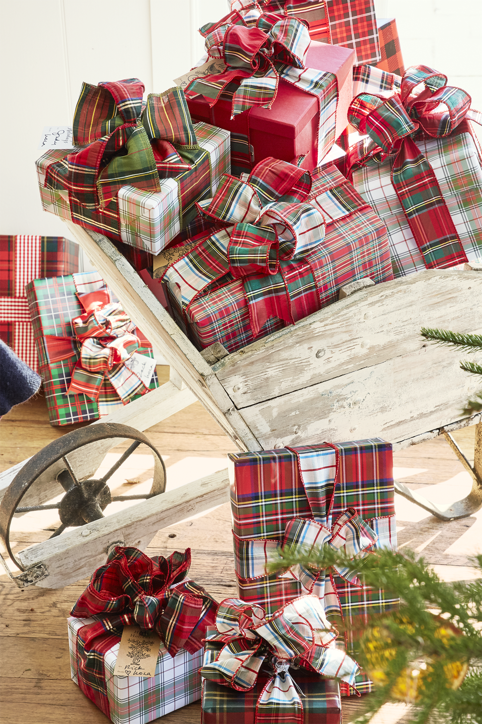 """<p>Wrap your gifts in different but matching patterns of plaid, and display them in a wheelbarrow adjacent to the Christmas tree. </p><p><a class=""""link rapid-noclick-resp"""" href=""""https://www.amazon.com/s/ref=nb_sb_noss_2?url=search-alias%3Dhpc&field-keywords=plaid+gift+wrap&tag=syn-yahoo-20&ascsubtag=%5Bartid%7C10050.g.1247%5Bsrc%7Cyahoo-us"""" rel=""""nofollow noopener"""" target=""""_blank"""" data-ylk=""""slk:SHOP PLAID GIFT WRAP"""">SHOP PLAID GIFT WRAP</a></p>"""