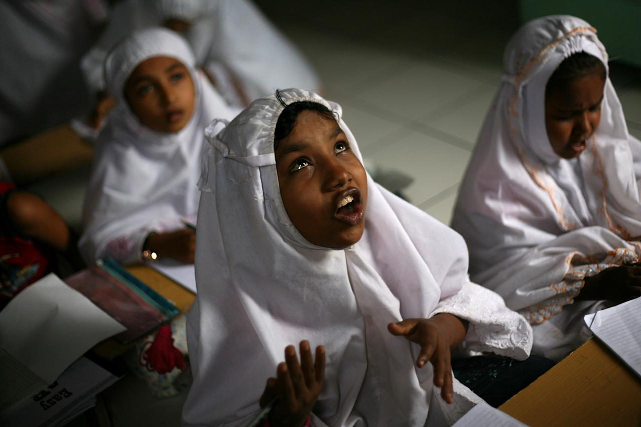 In this Oct. 11, 2013 photo, young ethnic Rohingya asylum seeker Senwara Begum from Myanmar, center, attends an English class at her temporary shelter in Medan, North Sumatra, Indonesia. Indonesia has been sympathetic to the Rohingya, and its president has sent a letter to his Myanmar counterpart calling for an end to the crisis. (AP Photo/Binsar Bakkara)