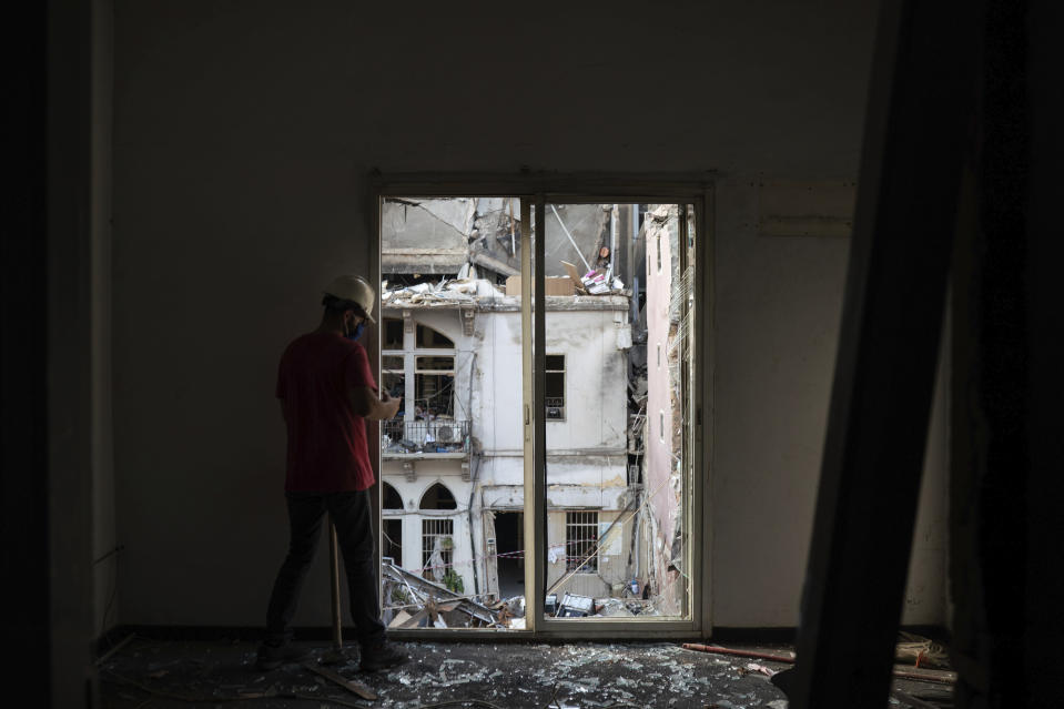 An engineer inspects a residential building heavily damaged in last week's explosion that hit the seaport of Beirut, Lebanon, Tuesday, Aug. 11, 2020. (AP Photo/Felipe Dana)
