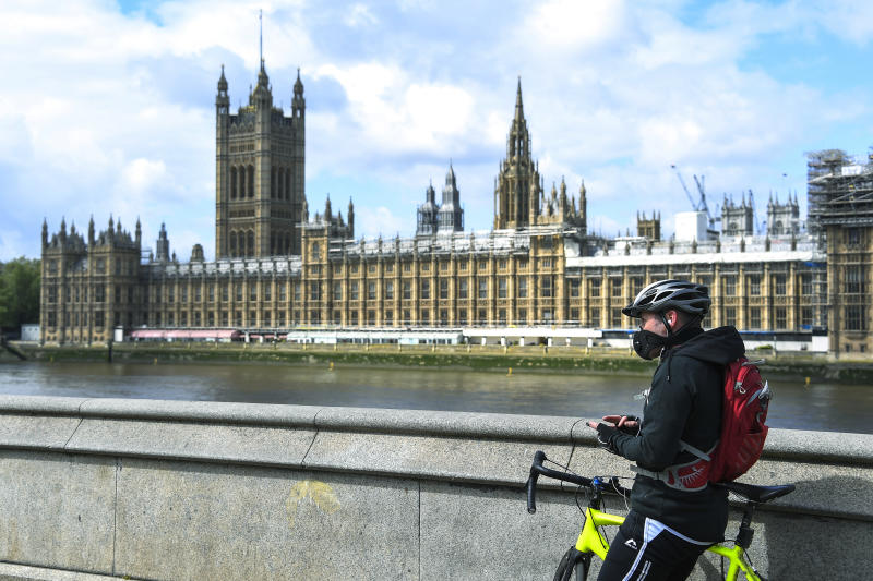 FILE - In this file photo dated Friday, May 1, 2020, a man stands with his bike, wearing a protective mask to protect against coronavirus, on the south bank of the River Thames, against the backdrop of the Houses of Parliament, in London, as the country continues its lockdown to curb the spread of coronavirus. The government has decided to scrap a remote-voting system used during the coronavirus pandemic, and has summoned lawmakers back to parliament on Tuesday June 2, 2020, but many aren't happy with the arrangements. (AP Photo/Alberto Pezzali, FILE)