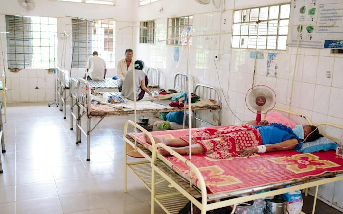 A patient lies on a bed in a hospital ward - Tom Greenwood/WaterAid