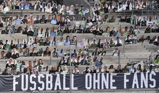 """Thousands of cardboards with photos of Borussia Moechengladbach soccer fans are displayed on the stands at he stadium in Moenchengladbach, Germany, Tuesday, Aug. 4, 2020. A banner reads """"football without fans"""". Because of the COVID-19 pandemic, all Bundesliga matches took place behind closed doors. The German football league, DFL, works on a concept for the new season with fans returning to the stadiums. (AP Photo/Martin Meissner)"""