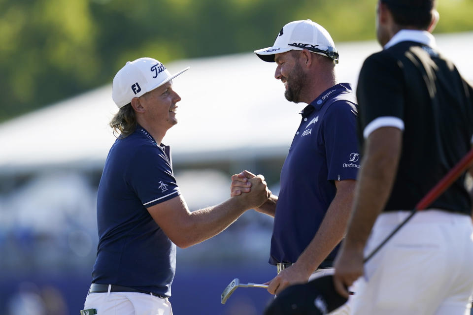Cameron Smith, of Australia, left, celebrates with his teammate Marc Leishman, of Australia, after winning the PGA Zurich Classic golf tournament at TPC Louisiana in Avondale, La., Sunday, April 25, 2021. (AP Photo/Gerald Herbert)