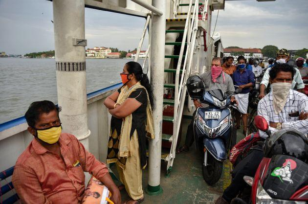People wearing masks travel in a ferry during the coronavirus pandemic in Kochi, May 29, 2020.