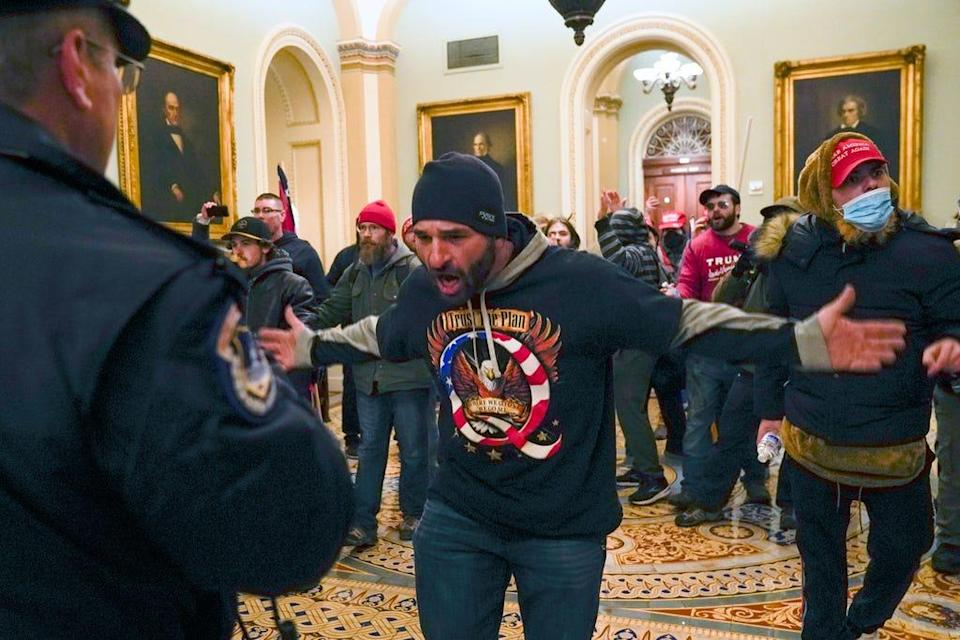 In this Jan. 6, 2021, file photo, Trump supporters, including Doug Jensen, center, confront U.S. Capitol Police in the hallway outside of the Senate chamber at the Capitol in Washington. Some followers of the QAnon conspiracy theory are now turning to online support groups and even therapy to help them move on, now that it's clear Donald Trump's presidency is over.