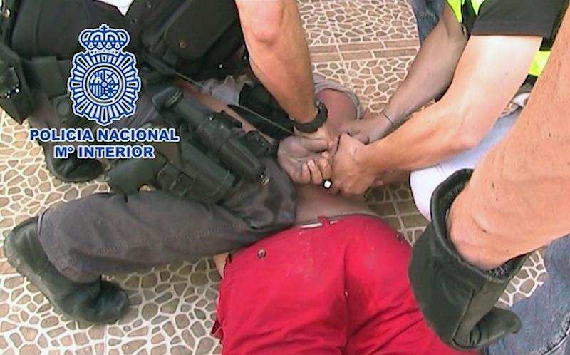 In this photo released Sunday May 12, 2013, by the Spanish National Police and British Serious Organised Crime Agency (SOCA), showing the moment British fugitive Andrew Moran is arrested Friday May 10, 2013, as he relaxed next to the pool of a luxury villa in Alicante, Spain. Moran has been on the run since 2009 when he assaulted four security guards, vaulted over the court dock during his trial in England and escaped, and was listed among the most wanted British fugitives who was known to be on the loose in Spain. (AP Photo / Spanish National Police/SOCA)