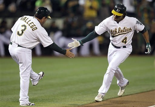 Oakland Athletics' Coco Crisp, right, is congratulated by third base coach Mike Gallego after Crisp hit a home run off Seattle Mariners' Blake Beavan during the first inning of a baseball game Friday, Sept. 28, 2012, in Oakland, Calif. (AP Photo/Ben Margot)