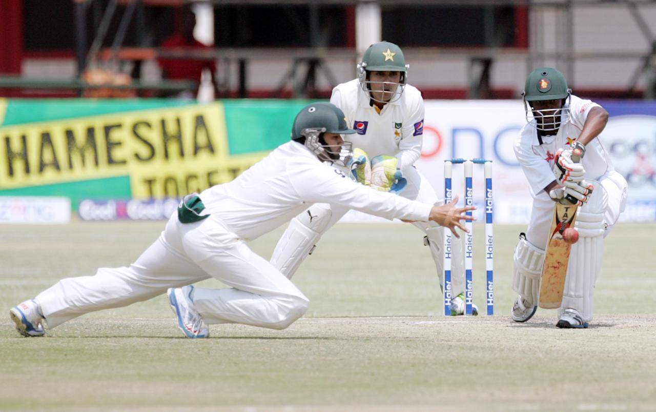 Pakistan's short-leg fielder Azhar Ali (L) attempts a catch off the batting of Richmond Mutumbami (R) during the fourth day of the second test match between Pakistan and Zimbabwe at the Harare Sports Club September 13, 2013.  AFP PHOTO / JEKESAI NJIKIZANA        (Photo credit should read JEKESAI NJIKIZANA/AFP/Getty Images)