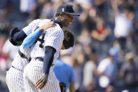 New York Yankees relief pitcher Aroldis Chapman (54) smiles as he and catcher Gary Sanchez walk out to greet teammates after escaping a jam when Oakland Athletics designated hitter Sean Murphy hit into a triple play in the ninth inning of a baseball game, Sunday, June 20, 2021, at Yankee Stadium in New York. (AP Photo/Kathy Willens)