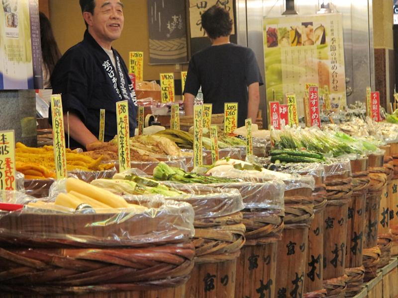 In this August 2012 photo, a vendor mans a stand selling a wide variety of pickled vegetables in the Nishiki-koji market arcade in Kyoto, Japan. Many of the market's merchants offer free samples to entice customers. (AP Photo/Adam Geller)