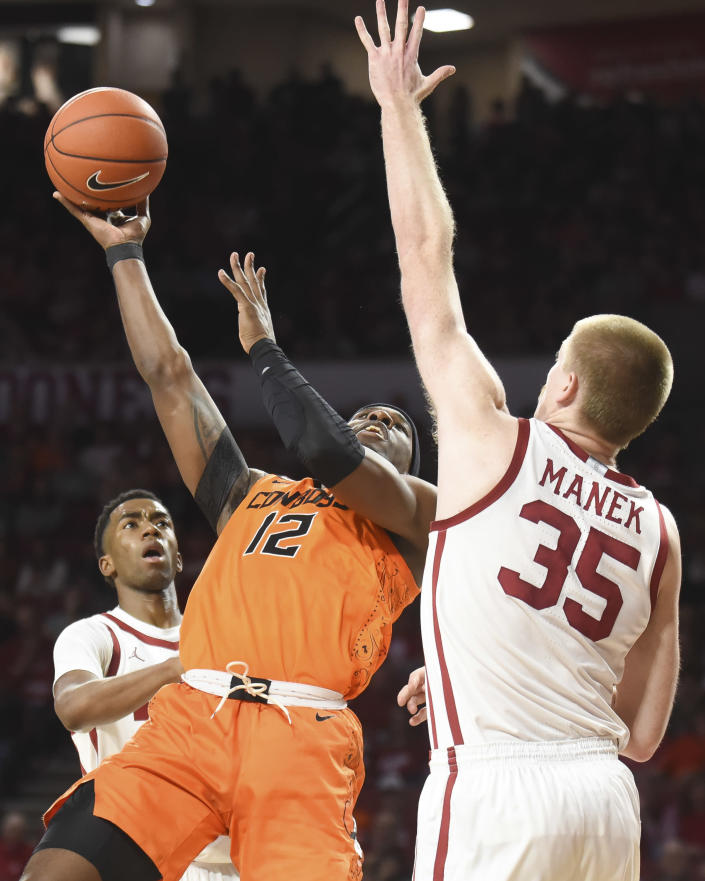 Oklahoma St forward Cameron McGriff (12) shoots the ball over Oklahoma forward Brady Manek (35) during the first half of an NCAA college basketball game in Norman, Okla., Saturday, Feb. 1, 2020. (AP Photo/Kyle Phillips)