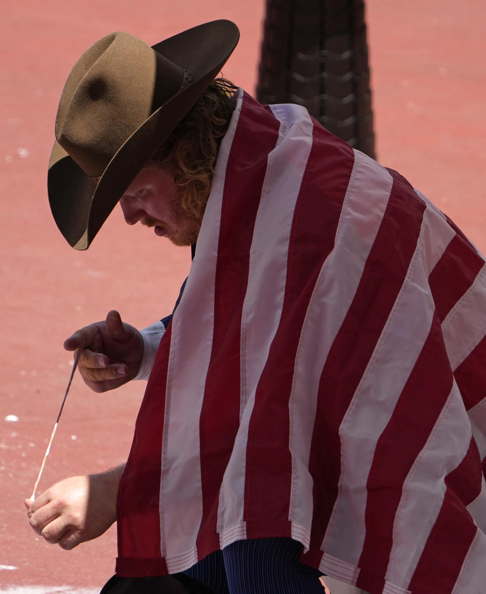 Ryan Crouser, of United States takes off his finger tape after winning the gold in the final of the men's shot put at the 2020 Summer Olympics, Thursday, Aug. 5, 2021, in Tokyo, Japan. (AP Photo/Charlie Riedel)