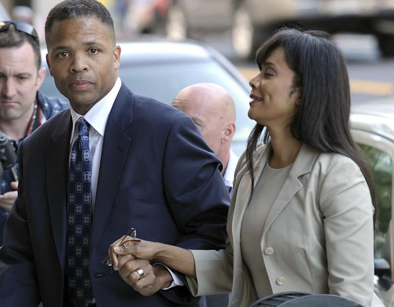 FILE - In this Aug. 14, 2013, file photo, former Illinois Rep. Jesse Jackson Jr. and his wife, Sandra, arrive at federal court in Washington. The U.S. Marshals service saID Friday, Sept. 20, 2013, that it's canceling a high-profile auction of clothing and memorabilia belonging to the convicted former congressman and his wife because of questions about the authenticity of some items. The U.S. Marshals Service began the auction earlier this week to recoup part of the $750,000 in campaign funds the former congressman and his wife illegally spent on memorabilia, furs, vacations and other personal items. (AP Photo/Susan Walsh, File)