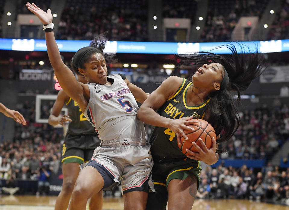 Connecticut's Crystal Dangerfield, left, fouls Baylor's Te'a Cooper during the first half of an NCAA college basketball game Thursday, Jan. 9, 2020, in Hartford, Conn. (AP Photo/Jessica Hill)