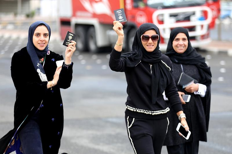 Kuwaiti women flash their passports as they arrive to cast their votes at a polling station in Kuwait City on November 26, 2016 (AFP Photo/Yasser Al-Zayyat)