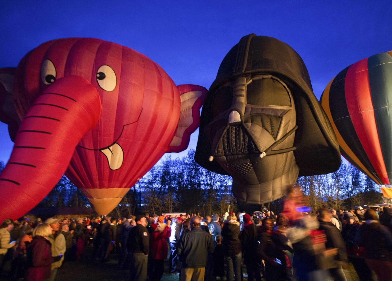 Hot air balloons, shaped like the Nelly-B and Darth Vader characters, are displayed during a night glow on the evening of Day 3 of the Canadian Hot Air Balloon Championships in High River September 27, 2013. Spectators had the opportunity to walk among the balloons which do not actually launch. The launches during the day will determine qualifiers for the World Hot Air Balloon Championships in Sao Paulo in 2014. REUTERS/Mike Sturk (CANADA - Tags: SOCIETY)