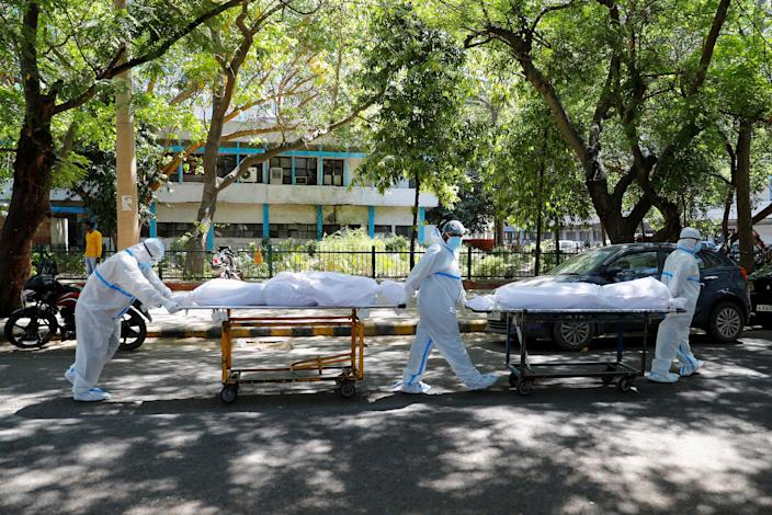 Image: Healthcare workers carry the bodies of people suffering from Covid-19 outside New Delhi's Gluteg Bahadur Hospital (Adnan Abidi / Reuters)