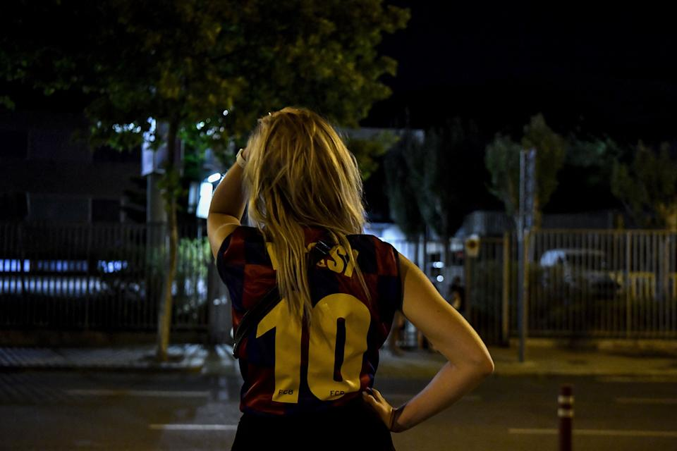 A fan wearing a jersey of Barcelona's Argentinian forward Lionel Messi gestures as supporters gather in front of the Camp Nou stadium in Barcelona on August 5, 2021. - Lionel Messi will end his 20-year career with Barcelona after the Argentine superstar failed to reach agreement on a new deal with the club, the Spanish giants announced on August 5, 2021. (Photo by Pau BARRENA / AFP) (Photo by PAU BARRENA/AFP via Getty Images)