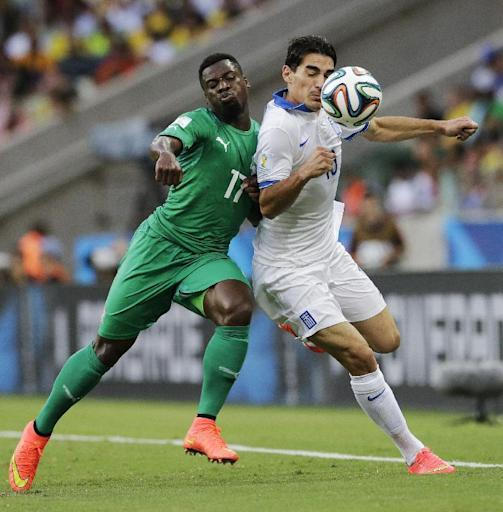 Ivory Coast's Serge Aurier pushes off Greece's Lazaros Christodoulopoulos during the group C World Cup soccer match between Greece and Ivory Coast at the Arena Castelao in Fortaleza, Brazil, Tuesday, June 24, 2014. (AP Photo/Bernat Armangue)