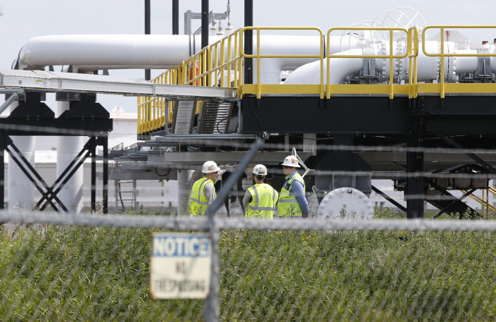 """FILE - In this June 29, 2018 file photo, workers are visible at the Superior terminal of Enbridge Energy in Superior, Wis. Enbridge says the upgrade and expansion of its Line 3 pipeline across Minnesota is complete and will become operational on Friday, Oct. 1, 2021. The Canadian-based company's President and CEO Al Monaco said in a statement Wednesday that the pipeline """"will soon deliver the low-cost and reliable energy that people depend on every day."""" (AP Photo/Jim Mone File)"""