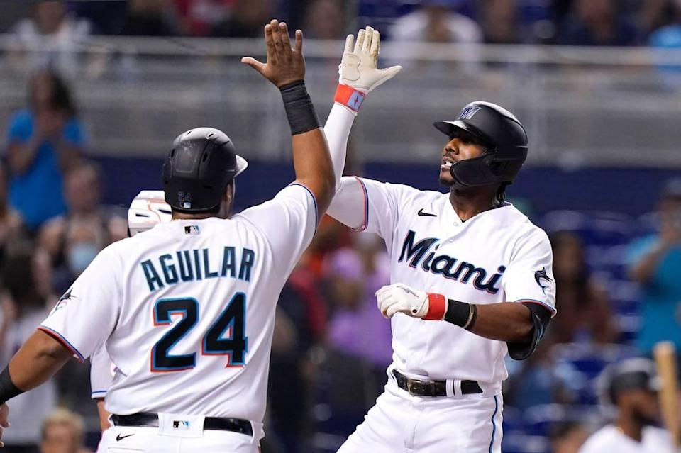 Miami Marlins' Lewis Brinson, right, is met by Jesus Aguilar (24) after hitting a grand slam off New York Mets starting pitcher Tylor Megill during the first inning of a baseball game, Monday, Aug. 2, 2021, in Miami. (AP Photo/Lynne Sladky)