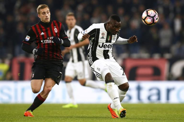 AC Milan's midfielder Gerard Deulofeu (L) fights for the ball with Juventus' midfielder Kwadwo Asamoah during the Italian Serie A football match Juventus Vs AC Milan on March 10, 2017